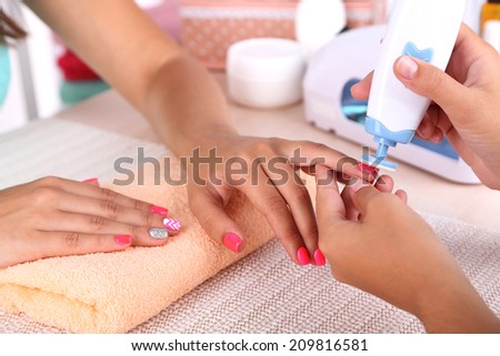 Young woman is getting manicure in beauty salon, close-up #209816581