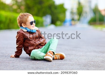 stylish boy in leather jacket posing on the ground Royalty-Free Stock Photo #209839360