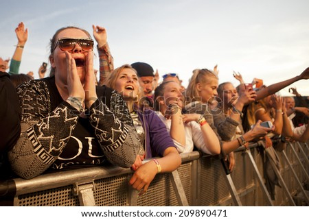 Traena, Norway - July 11 2014: people watching the concert of the Swedish pop-techno band Den Svenska Bjornstammen at the Traenafestival, music festival taking place on the small island of Traena #209890471