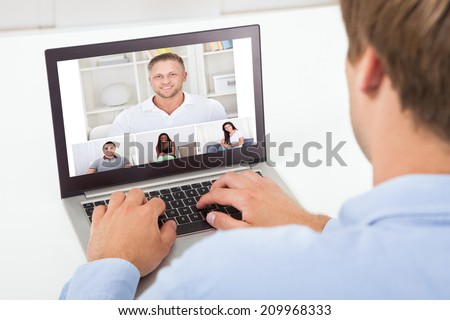 Rear view of businessman video conferencing on computer at desk in office #209968333