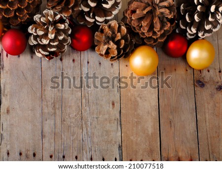 Christmas background of pine cones and Christmas balls on a rustic wooden surface. The decorations are gold and red. Some of the pine cones have fake snow tipped scales. Plenty of copy space #210077518