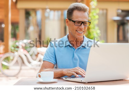 Man working outdoors. Cheerful mature man working at laptop and smiling while sitting at the table outdoors with house in the background  #210102658