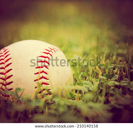 a square photo of a baseball in a grass background toned with a vintage retro instagram filter