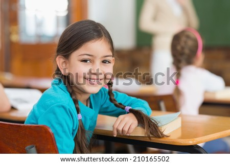 Cute pupil smiling at camera at her desk in classroom at the elementary school #210165502