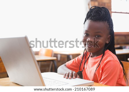 Cute pupil using laptop in classroom at the elementary school #210167089