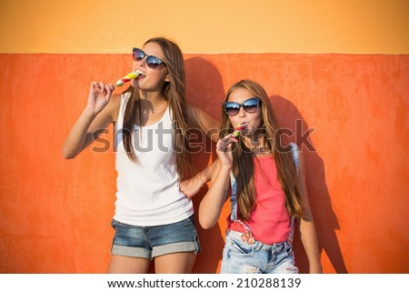 two girls with ice-cream on background wall #210288139