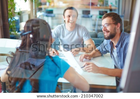 Young business partners discussing ideas or project at meeting in office Royalty-Free Stock Photo #210347002