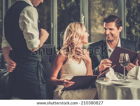 Cheerful couple with menu in a restaurant making order #210380827