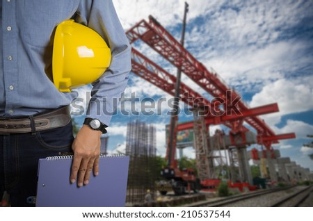 Engineer holding yellow helmet for workers security on background of construction cranes  lifts load. #210537544