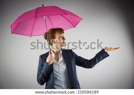 Smiling businesswoman holding pink umbrella on grey background #210586189