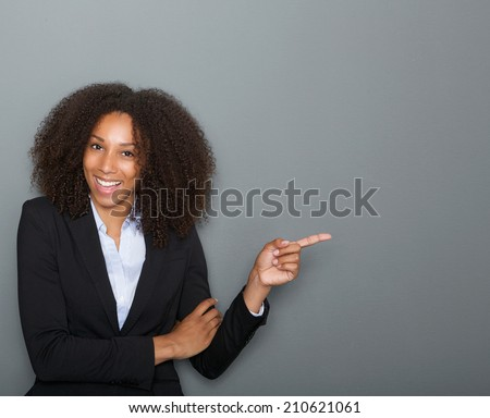 Close up portrait of a smiling business woman pointing finger showing copy space #210621061