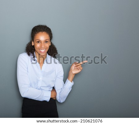 Close up portrait of a confident business woman pointing finger on gray background #210621076