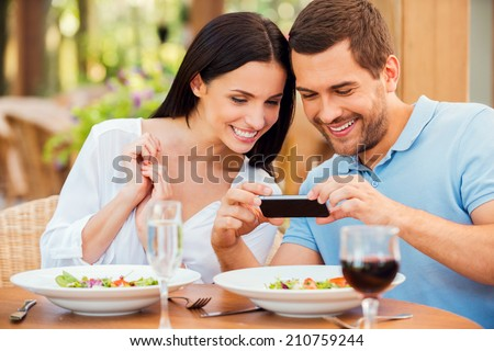 I want to share this picture with friends. Happy young loving couple taking pictures of their food and smiling while relaxing in outdoors restaurant together