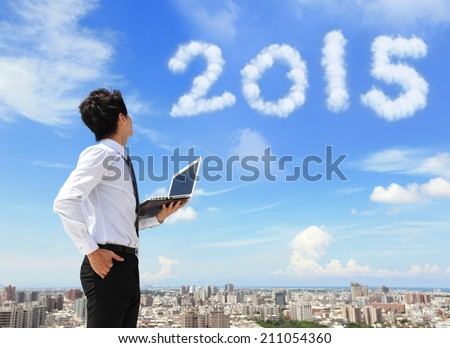 Young business man using laptop and look to 2015 year text with blue sky and cloud and cityscape in the background, asian Royalty-Free Stock Photo #211054360