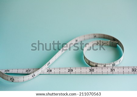 Close up still life detail view of a soft tailor measuring tape laying in a curly shape on a plain blue background, interior. Trade tools and objects for exact measure taking. #211070563
