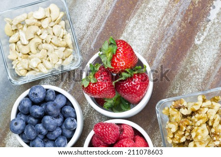 Healthy snack foods with small bowls of raspberries, blueberries, strawberries, cashews and walnuts Royalty-Free Stock Photo #211078603