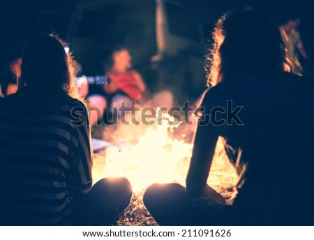 People sit at night round a bright bonfire #211091626