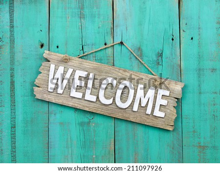 Rustic wood welcome sign hanging on weathered antique teal blue door;  wooden sign with painted background