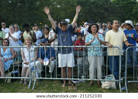 NEW YORK - JUNE 25:  A man gestures as he and others pray at the Greater New York Billy Graham Crusade in Flushing Meadow Corona Park June 25, 2005 in the Queens borough of New York City. #211252330