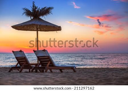 Vivid sunrise on a beautiful sandy beach with sunshade  #211297162