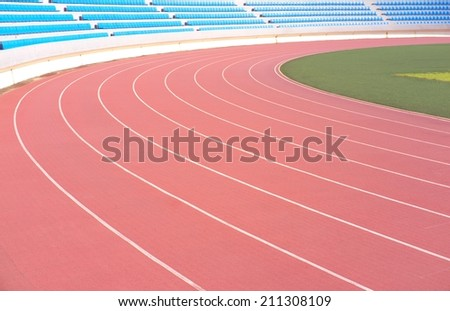 athletic running track lanes with rows of stadium seats in background #211308109