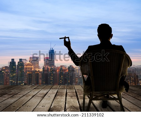 Silhouette of businessman sit on chair and hold a cigar and looking at the city in night. Royalty-Free Stock Photo #211339102