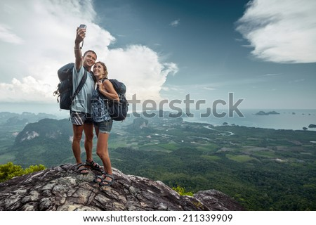 Two hikers taking selfie on top of the mountain