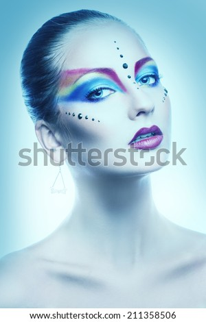 Sexy portrait of female with multicolor make up in cold tones in studio #211358506