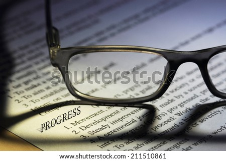 """Eyeglasses on a paper , focus on a 3D word """"Progress"""" with shallow depth of field #211510861"""
