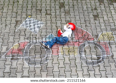 Creative leisure for children: Funny little child of four years having fun with race care picture drawing with chalk.