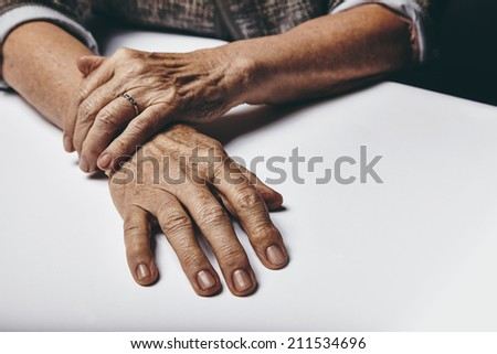 Close-up image of senior woman sitting by a table with focus on her hands. Old female hands on a desk. #211534696