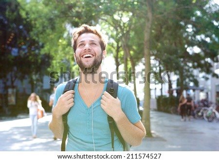 Close up portrait of a handsome young man walking outdoors with backpack #211574527