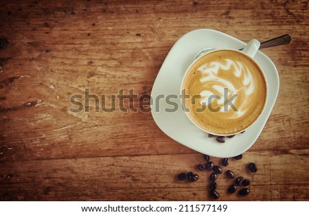 Cup of art latte or cappuccino coffee with retro filter effect Royalty-Free Stock Photo #211577149