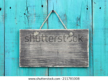 Blank rustic wood sign hanging on antique teal blue wooden background; distressed background with copy space