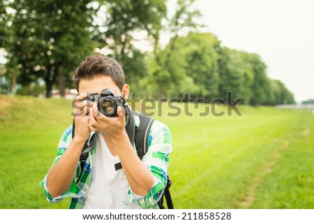 Closeup of young hipster man with digital camera outdoors. Young male photographer photographing nature on summer day.