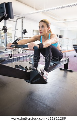 Full length of a young woman working on fitness machine at the gym #211911289