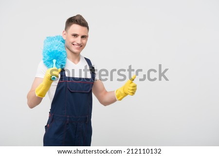 Half-length portrait of young happy smiling dark-haired janitor wearing white T-shirt overalls and yellow rubber gloves holding blue duster on the shoulder satisfied with his work. Isolated on white #212110132