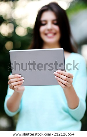 Portrait of a woman holding tablet computer. Focus on tablet computer #212128654