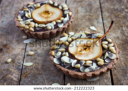 chocolate tartlets with pear and nuts on a wooden background Royalty-Free Stock Photo #212222323