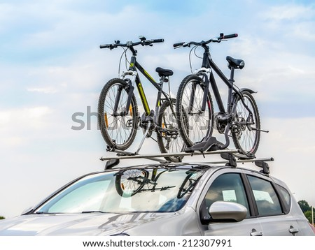 Passanger car with two bicycle mounted to the roof Royalty-Free Stock Photo #212307991