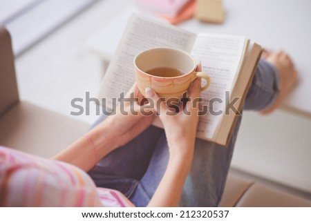 Close-up of female hands holding teacup in front of opened book #212320537