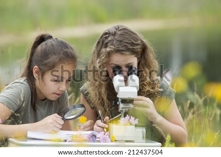 Pretty young girls having outdoor science lesson  exploring nature  #212437504