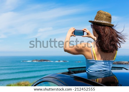 Happy woman taking photos to the sea with smartphone camera on car summer travel vacation to the coast. Brunette girl  leaning out vehicle sunroof towards the ocean.