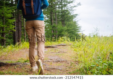 Unrecognizable hiker woman going on path in the summer forest. Legs view. #212547415