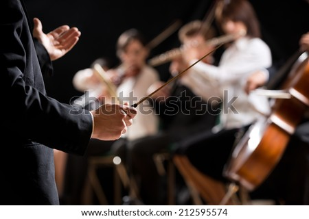 Conductor directing symphony orchestra with performers on background, hands close-up. #212595574