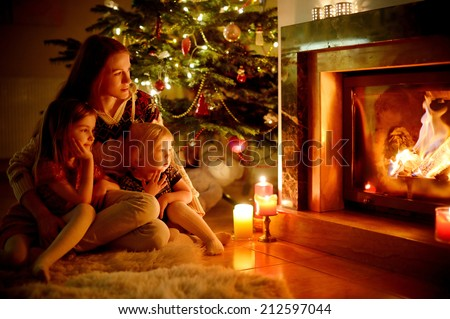 Young mother and her two little daughters sitting by a fireplace in a cozy dark living room on Christmas eve #212597044