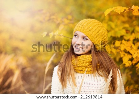 Portrait of beautiful girl with scarf and hat in yellow autumn nature #212619814