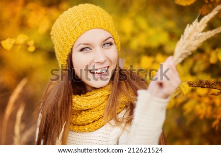 Portrait of beautiful girl with scarf and hat in yellow autumn nature #212621524