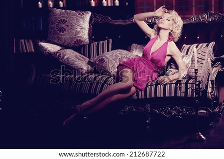 Luxury woman. Young fashionable slim pretty woman in the bedroom. Blonde in a luxurious interior.