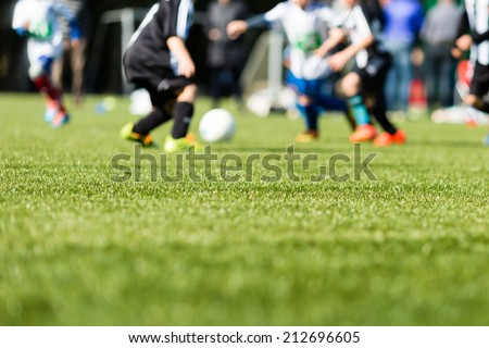Picture of kids soccer training match with shallow depth of field. Focus on foreground. Royalty-Free Stock Photo #212696605